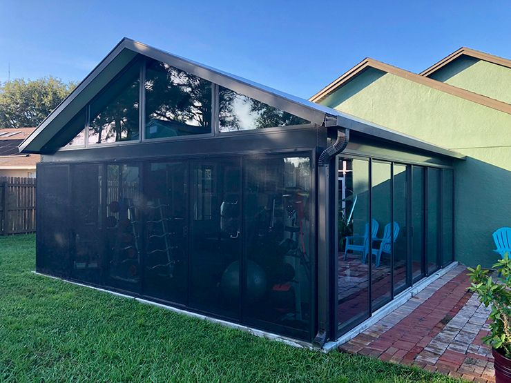 Huge bronze sunroom with trapezoid windows and double stacking sliders