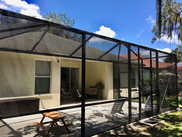 Large screen enclosure with hip style screen roof and concrete patio