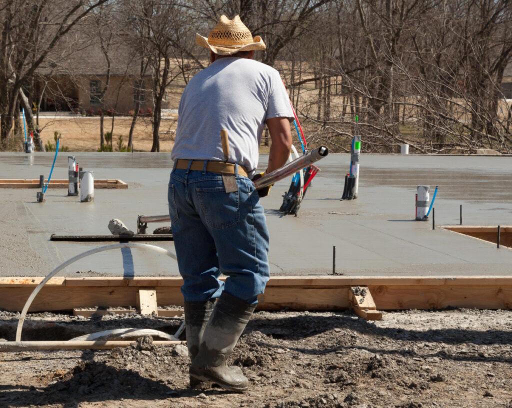 Concrete contractor bull floating concrete floor before house build