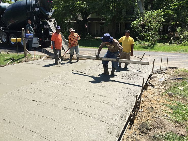 Concrete driveway contractors using screed board and come alongs to place the concrete.