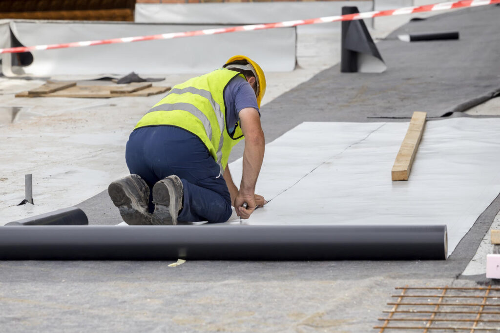 Roofing contractor cutting roofing membrane for installation