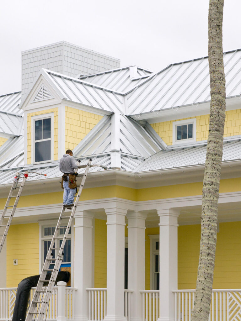 Roofing contractor performing repair on standing seam metal roof beach house