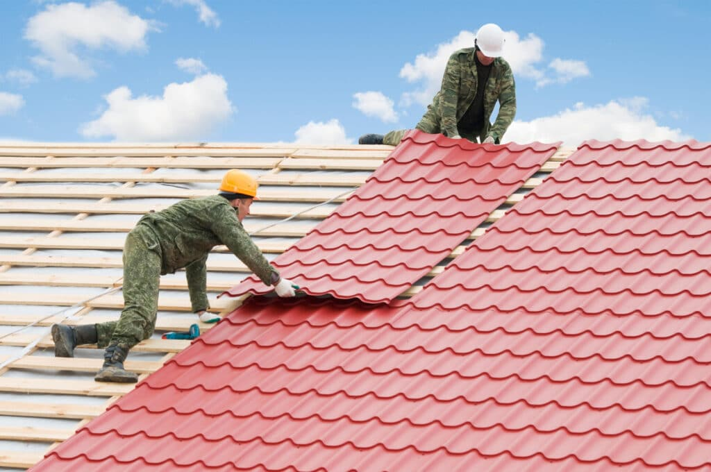 Roofing contractors installing metal roof tile sheets