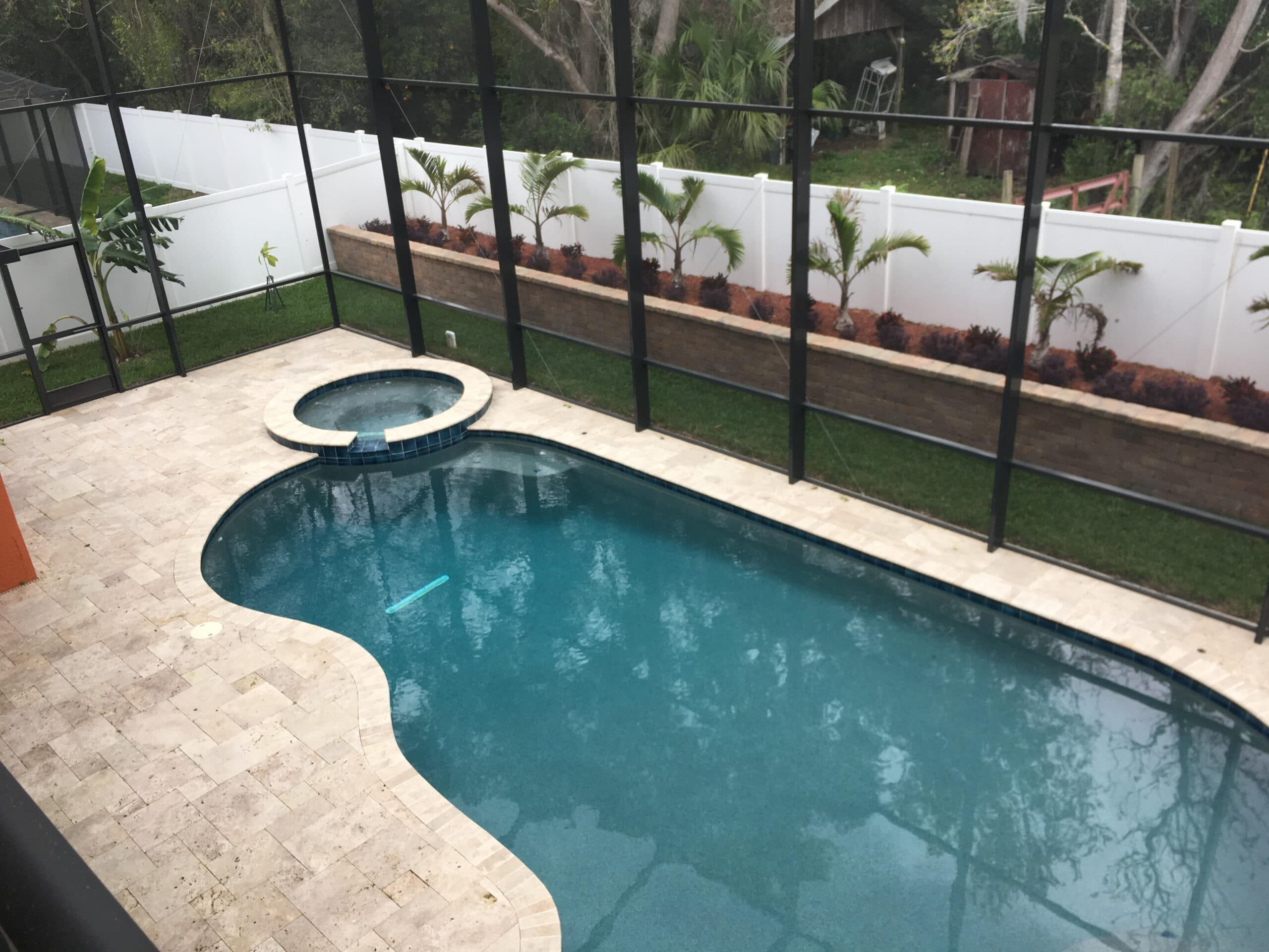 Bronze two story pool enclosure overhead view with travertine pool deck