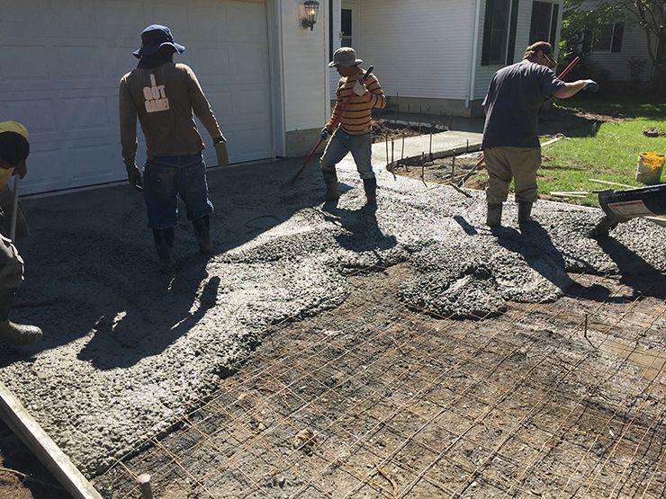 Concrete driveway contractors placing concrete over steel mesh.