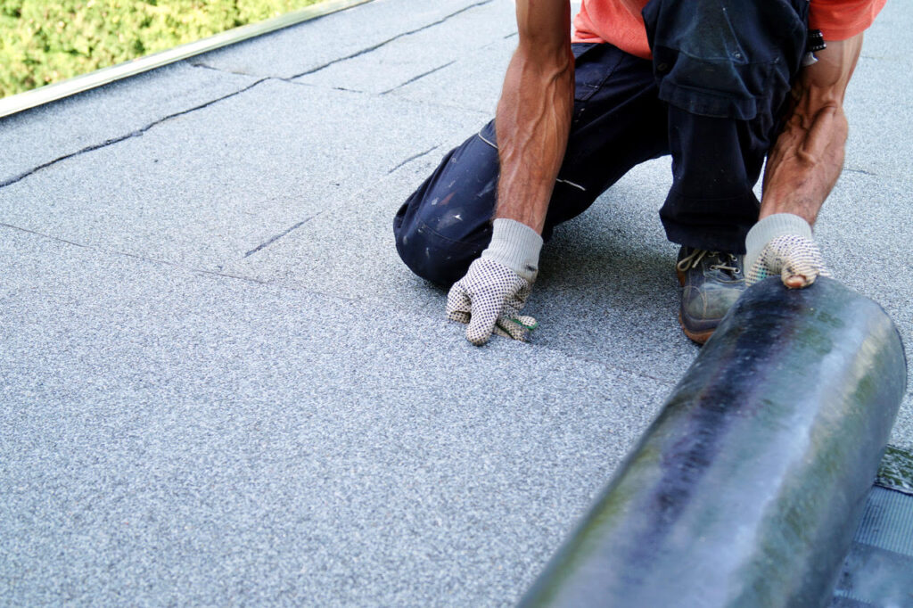 Roll roofing contractor performing installation on flat roof