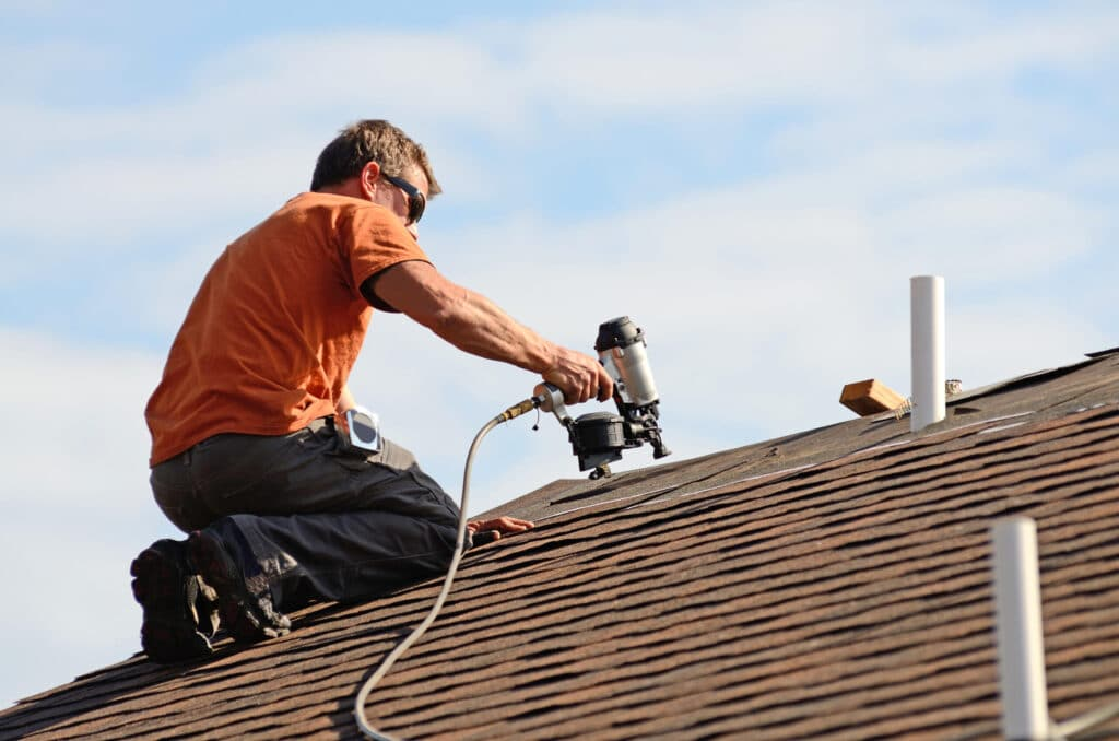 Roofing contractor using nail gun to install asphalt shingle roof