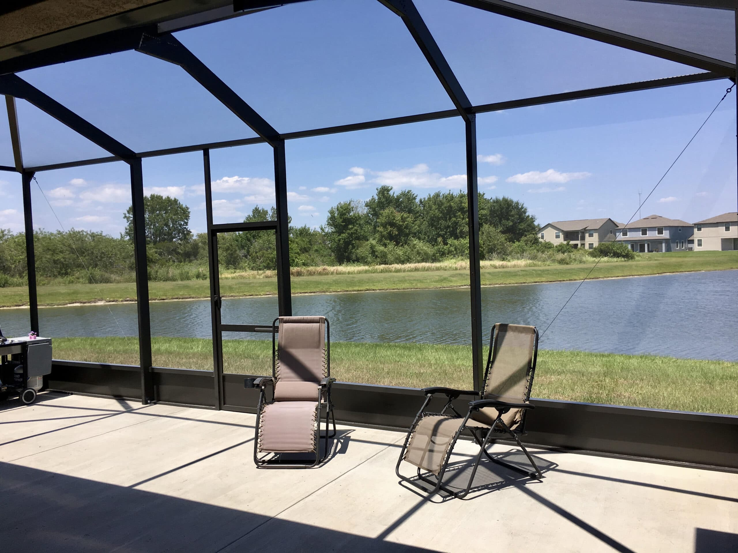 Bronze screen enclosure with concrete patio and lake view