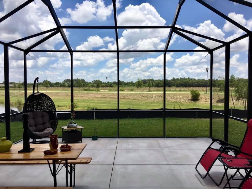 Bright blue sky with bronze screen enclosure and concrete patio