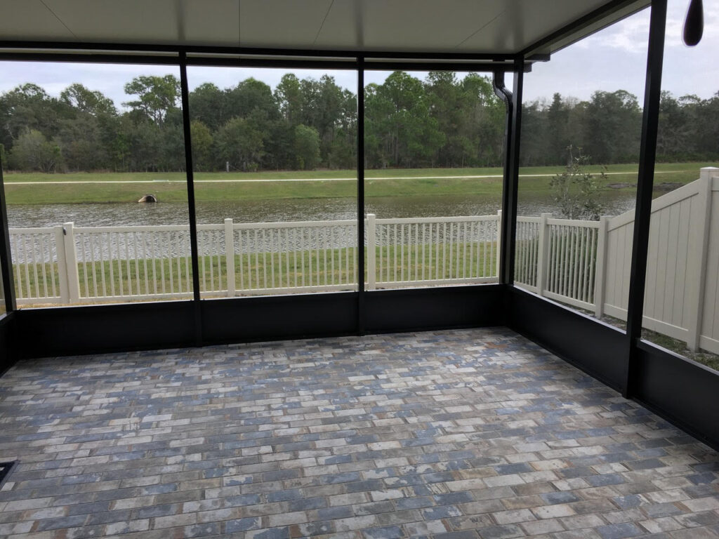 Lake front screen room with running bond tile flooring and insulated elite roof panels