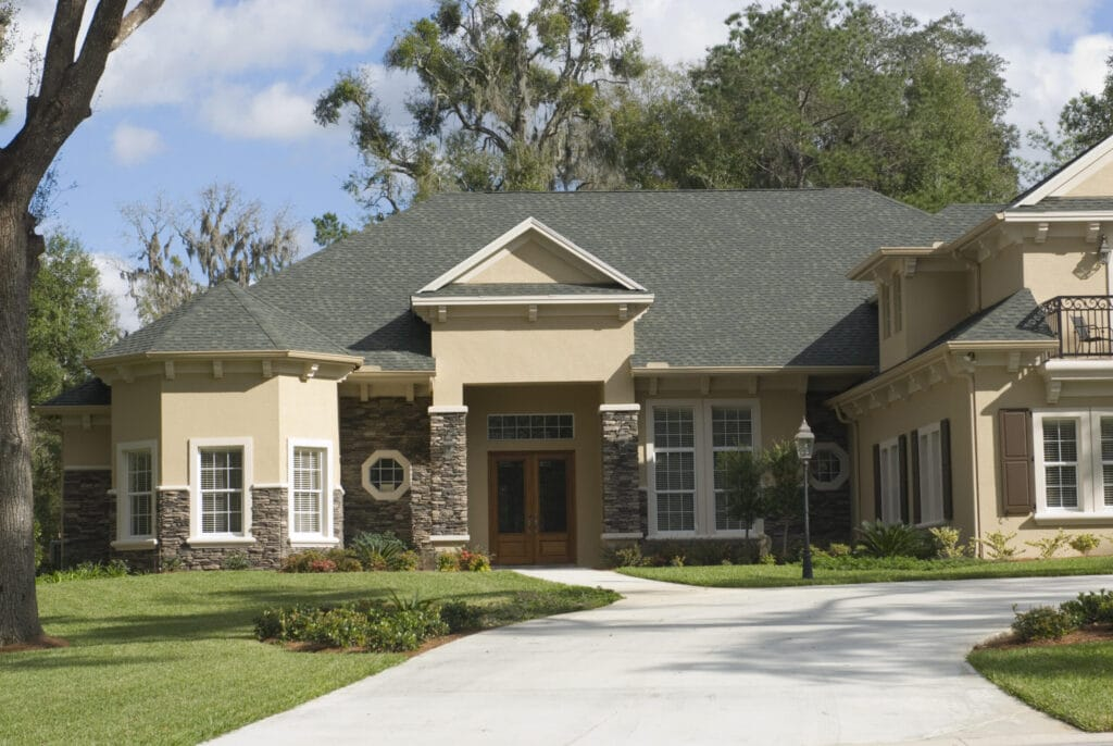 Shingle roof with vented ridge, landscaped yard and stone work on the house