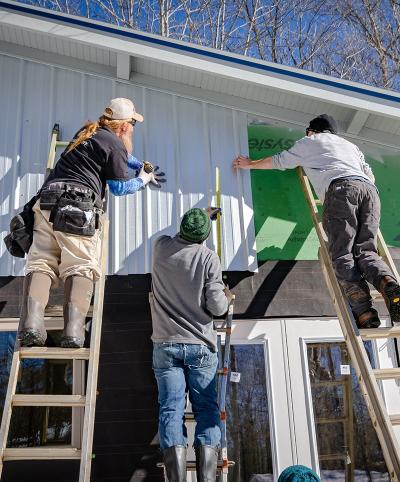 Installing metal siding by contractors on sunroom