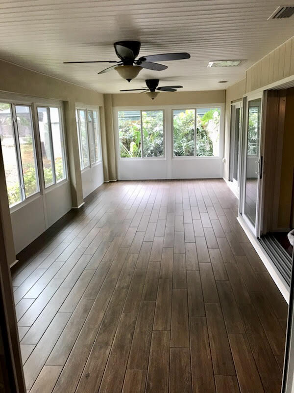 Lanai converted to sunroom with porcelain tile floor and sliding windows